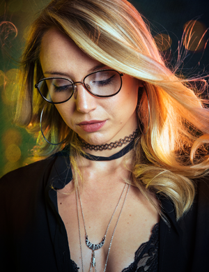 Pretty blonde lady looking down wearing glasses